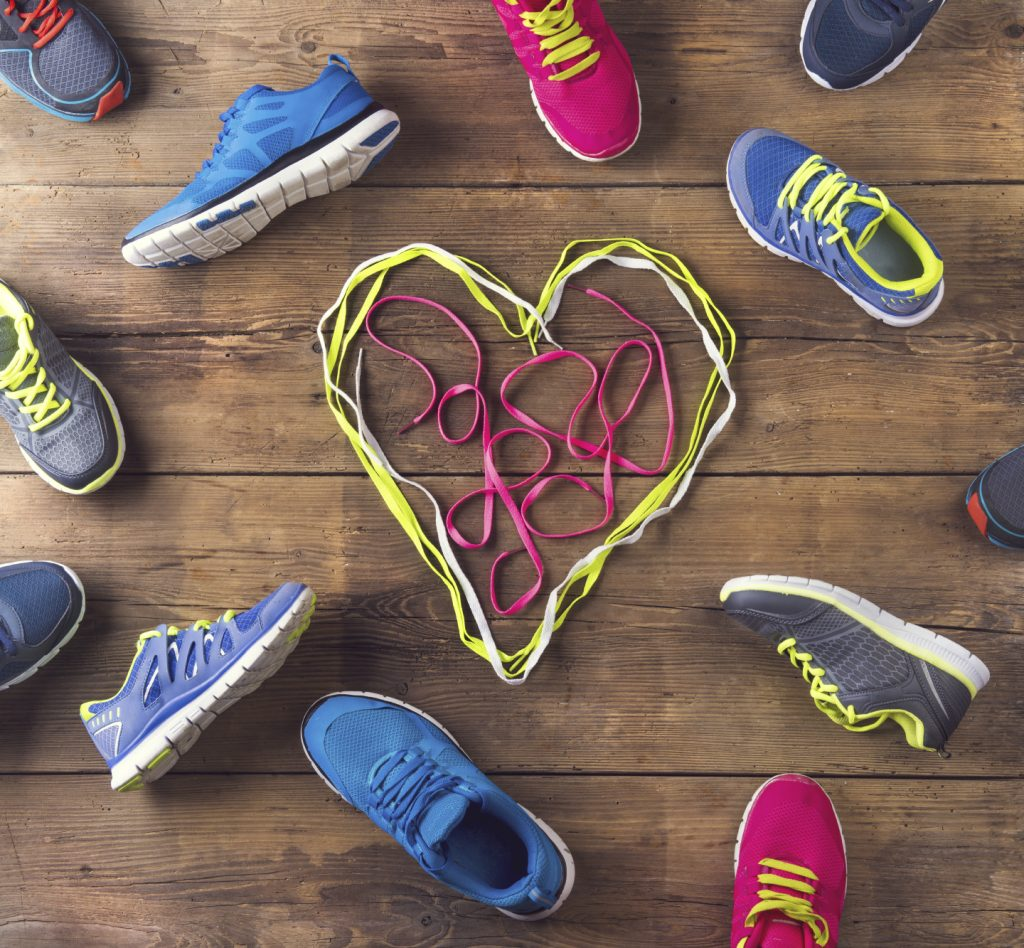 Various running shoes land shoelaces heart on a wooden floor background